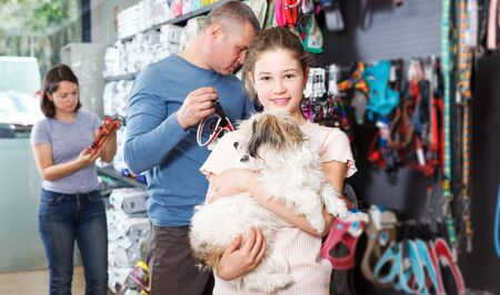 Portrait of happy girl with havanese pup while shopping with parents in pet store