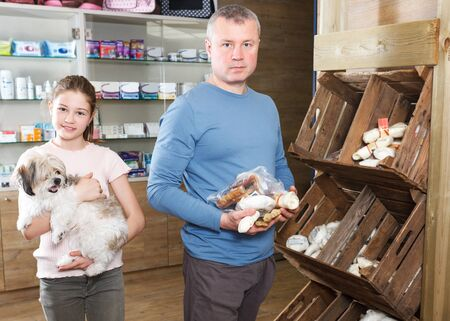 careful preteen girl with father choosing dog treats for their puppy in pet store