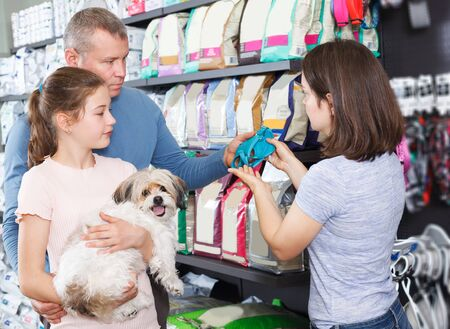 young family with preteen daughter visiting pet shop in search of accessories for their dog