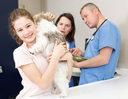 Smiling tweenager girl with her puppy visiting veterinarian clinic