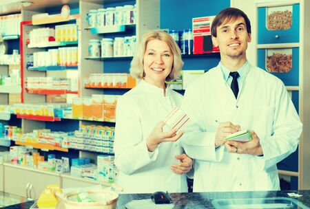 Team of caucasian pharmaceutist and technician working in chemist shop