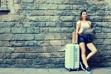 Happy young girl traveler with suitcase leaning against stone wall Stock Photo