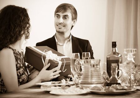 Woman giving present to positive man at table Standard-Bild