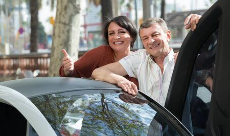 Cheerful mature couple standing near twizy electric with thumbs up outside