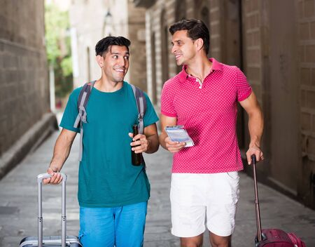 Glad men tourists walking with beer and luggage in Barcelona