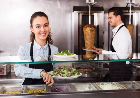 Happy adult restaurant staff posing at kebab counter and smiling Stock Photo
