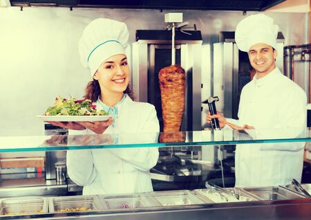 Two friendly smiling professional chefs with kebab and vegetables at bistro. Focus on woman