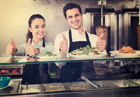 Smiling young restaurant staff posing at kebab counter and smiling Stock Photo