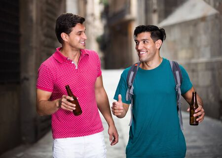 Two smiling guys friends are walking and drinking beer in Barcelona