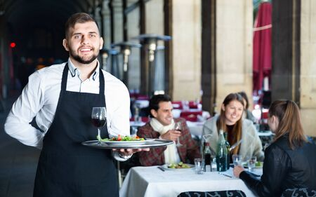 Portrait of glad cheerful positive  waiter with serving tray meeting restaurant guests Фото со стока - 125224178