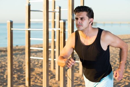 Serious strong man jogging during outdoor workout on beach Stock Photo