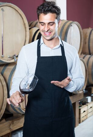 joyful smiling male seller wearing apron holding glass on wine tasting in cellar