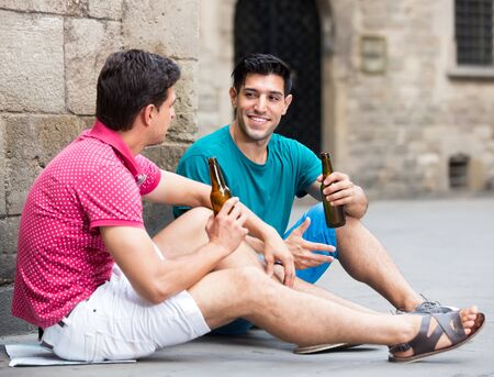 joyous male fans are drinking beer and talking about football outdoor in Barcelona outdoors Фото со стока