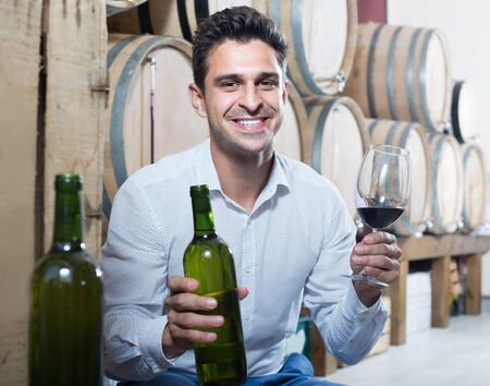Cheerful man customer holding glass and bottle of wine in shop with woods