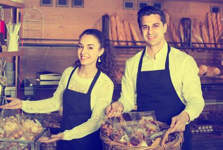 Friendly man and smiling girl offering fresh pastry and bread at bakery Stok Fotoğraf