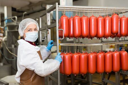 Female worker carrying raw sausages on racks in storage room at meat processing factory