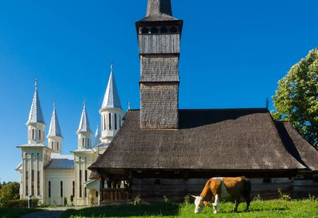 Traditional ancient wooden church with new building behind in Remetea Chioarului, Maramures, Romania Stock Photo