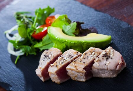 Appetizing light roasted tuna fillet served with avocado and greens