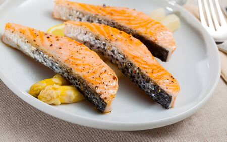 Delicious fish dish. Fried salmon fillets served with white asparagus and lemon slice Reklamní fotografie