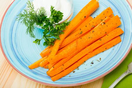 Picture of  tasty fried carrot sticks  and served with sour cream at plate