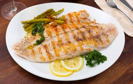 Healthy roasted sea perch fillet served on white plate with pickled asparagus and lemon Reklamní fotografie