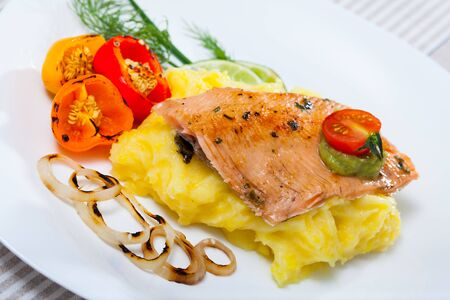 Tasty fried trout fillet with mashed potatoes, peppers, onion and greens on plate