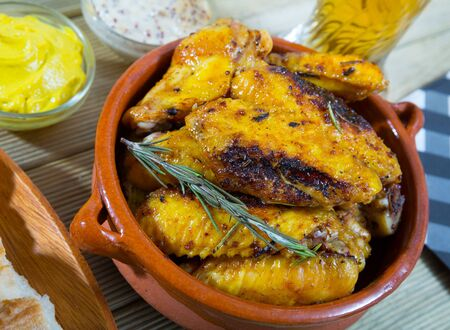Roasted chicken wings with golden crust served with mustard sauce and rosemary on clay bowl Reklamní fotografie