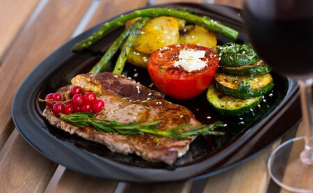 Image of veal with baked vegetables on the plate indoors.