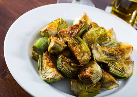 Vegetarian appetizer of sauteed in oil artichokes served on white plate