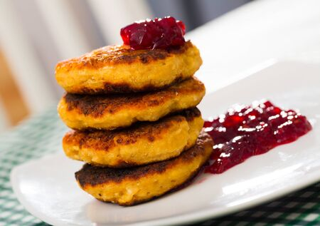 Image of stack of fried quark pancakes  with jam served at plate