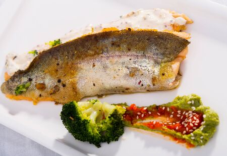 Delicious fried rainbow trout fillets with steamed broccoli and tartare sauce on white plate