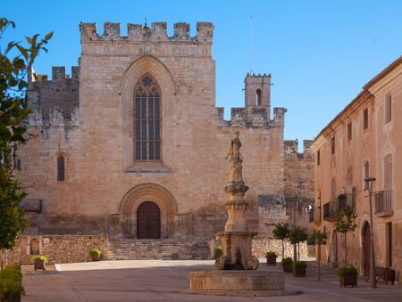 View of church main facade with Gothic stained glass window in courtyard of medieval Santes Creus Monastery, Aiguamurcia, Spain Stok Fotoğraf