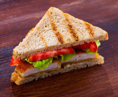 Tasty sandwich with  fried chicken nuggets, tomatoes and lettuce at plate