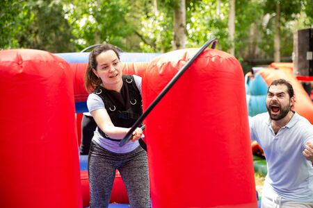 Portrait of emotional young woman putting hoop on inflatable pole during competition in outdoor amusement park