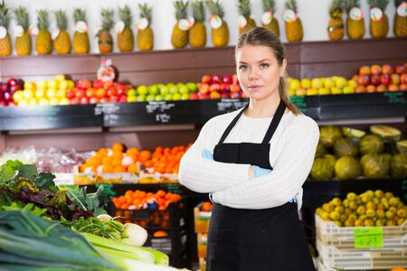 Portrait of young confident saleswoman of greengrocery standing near shelves with fruits