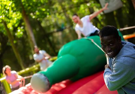 Nice African American man pulling rope of inflatable rodeo bottle, trying to throw female friend off in outdoor amusement park