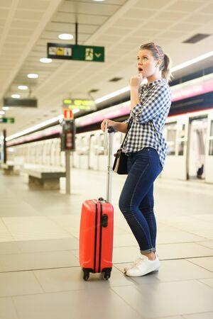 Portrait of surprised girl traveler waiting for train at metro station