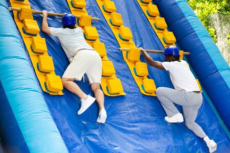 Mens competition on an inflatable slide Great race in an amusement park Imagens