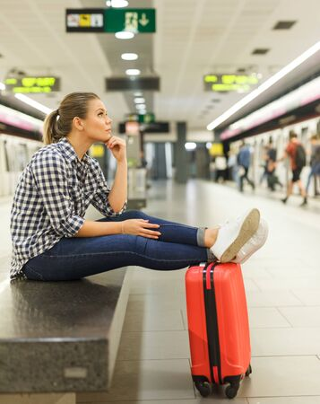 Attractive girl traveler waiting for train at metro station sitting on stone bench with legs stretched out on suitcase