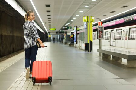 Back view of happy girl traveler walking along subway platform with red suitcase