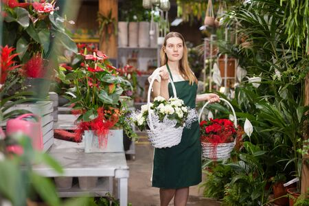 Portrait of skilled woman florist arranging flowers in pots at flower shop Imagens