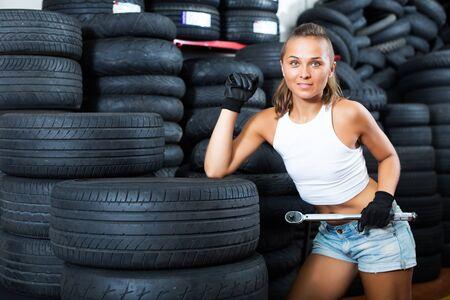 Lächelndes Mädchen, das als Automechaniker in der Werkstatt arbeitet