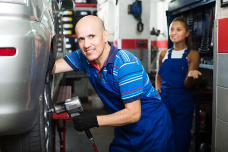 Happy mature mechanic man working with impact tire fitting tool in service point Stock Photo
