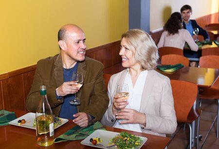Ordinary happy elderly couple having dinner at restaurant table