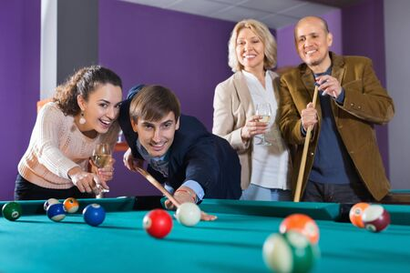 Relaxed smiling people playing billiard and darts as hanging out