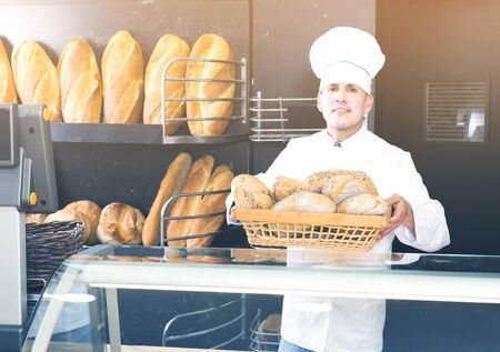 happy male employee offering fresh baguettes and buns in bakery