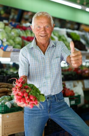 Happy older male purchaser enjoying shopping at local farmer market