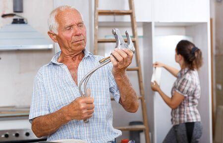 Anciano experimentado de pie con grifo mezclador en manos en su casa reparable