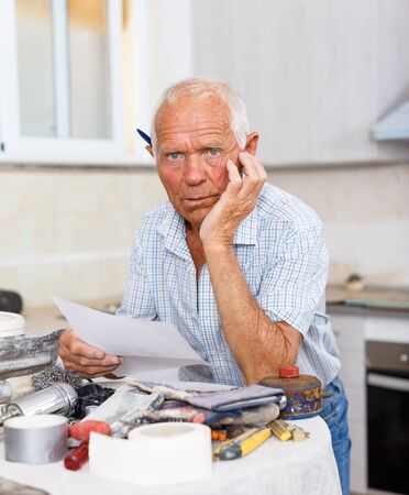 Pensive older man planning upcoming repairs, making list of works