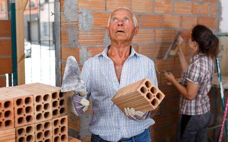 Anciano concentrado trabajando con su hija en las renovaciones de su hogar, instalando una pared de ladrillo en el interior
